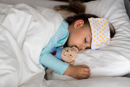 Authentic portrait sick cute caucasian little preschool baby girl in blue sleep with compress on forehead on white bed. child resting at lunchtime. care, medicine and health, Childhood, life concept