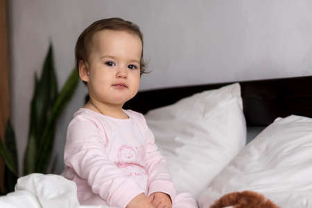 Authentic portrait caucasian little infant chubby baby girl or boy in pink sleepy upon waking looking at camera smiling cute and grimaces in white bed. Child care, Childhood, Parenthood, life concept Фото со стока