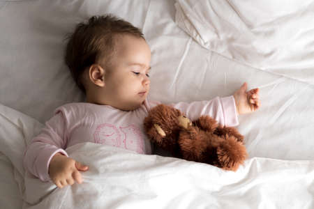Authentic portrait cute caucasian little infant chubby baby girl or boy in pink sleepy upon waking with teddy bear looking at camera in white bed. Child care, Childhood, Parenthood, lifestyle concept Фото со стока