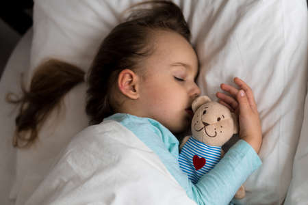 Authentic portrait sick cute caucasian little preschool baby boy in blue sleep with teddy bear on white bed. child resting at lunchtime. care, medicine and health, Childhood, Parenthood, life concept Фото со стока