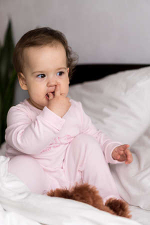Authentic portrait cute caucasian little infant chubby baby girl or boy in pink sleepy upon waking looking at camera in white bed. Child care, Childhood, Parenthood, lifestyle concept Фото со стока