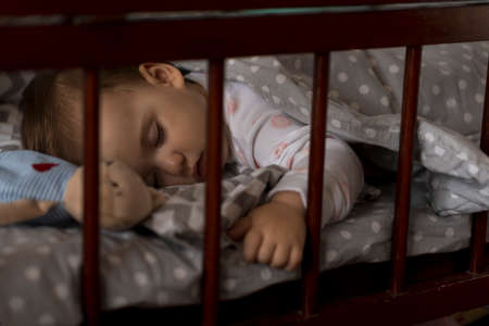 Cute cheerful little chubby baby girl sleeping sweetly in grey baby crib during lunch rest time in white and pink pajamas with teddy bear at home. Childhood, leisure, comfort, medicine, health concept