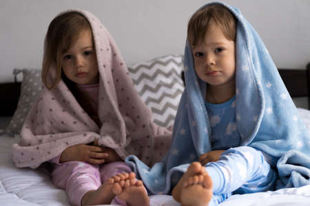 home, comfort, childhood, care, friendship - two little pretty authentic baby toddler sibling kids children sit on white bed look at camera wrapped in warm blue soft blanket, cozy sleepy mood indoors