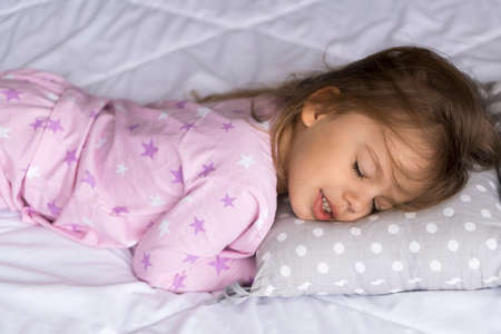 home, comfort, childhood, care, love, sweet dream- little pretty smiling happy authentic toddler sibling kid child girl in pajamas lie rest sleep on bed pillows with closed eyes soft cozy sleepy mood
