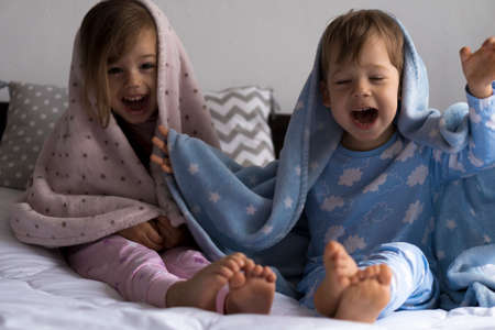 home, comfort, childhood, care, friendship - two funny happy authentic baby toddler sibling kids children sit on white bed look at camera wrapped in warm blue soft blanket, cozy sleepy mood indoors Stockfoto