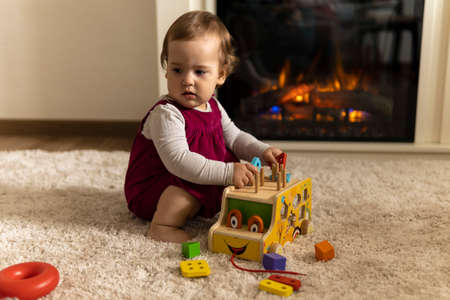 childhood, development, skills, motility games - little authentic child baby toddler girl composes sorts colored shapes playing wooden toy car sorter sit on mat carpet floor indoors room at cozy home