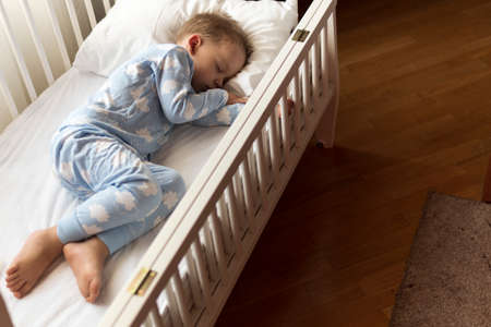top view Cute little 2-3 years preschool baby boy kid sleeping sweetly in white crib during lunch rest time in blue pajama with pillow at home. Childhood, leisure, comfort, medicine, health concept