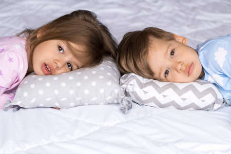 home, comfort, childhood, insomnia, sleeplessness, sweet dream - two sad tired toddler sibling kids children twins in pajamas lie rest can not sleep on bed pillows look at camera soft cozy sleepy mood