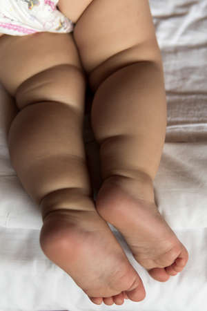 feet of toddler baby girl wearing diapers lying on white bed at home. plump legs of sleeping one year old caucasian child. kid sleeps in crib. home, comfort, childhood, care, love, sweet dream concept