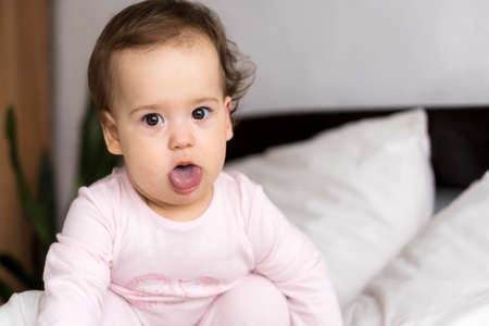 Authentic portrait cute caucasian little infant chubby baby girl or boy in pink sleepy upon waking looking at camera showing tongue in white bed. Child care, Childhood, Parenthood, lifestyle concept