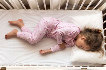 top view Cute little 3-4 years preschool baby girl kid sleeping sweetly in white crib during lunch rest time in pink pajama with pillow at home. Childhood, leisure, comfort, medicine, health concept Stockfoto