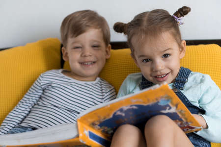 Two preshool, toddler children read large interesting book of fairy tales on yellow bed. Siblings little twins reader have fun, happy kid on quarantine at home. Friendship, family, education concept Stockfoto