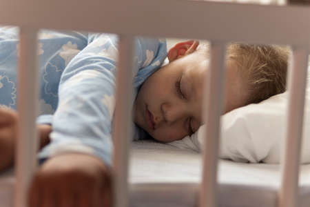 Cute cheerful little 2-3 years preschool baby boy kid sleeping sweetly in white crib during lunch rest time in blue pajama with pillow at home. Childhood, leisure, comfort, medicine, health concept