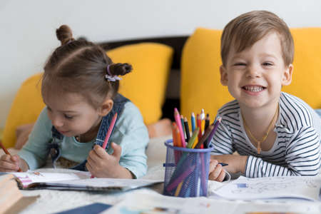 smart smiling preshool toddler children boy and girl draw with pencils lying on their stomach at yellow bed. little cute reader have fun, happy kid on quarantine at home. Friendship, family, education