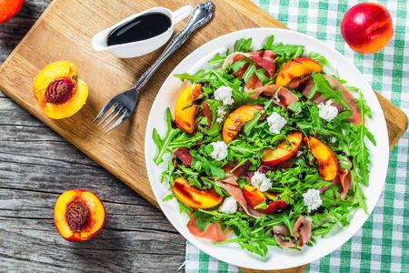 Perziken, arugula, prosciutto en geitenkaasalade met balsamico-azijn Stockfoto