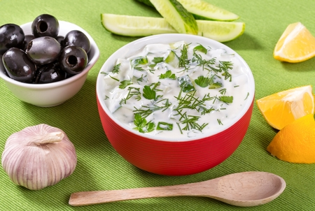 hombre sentado: fresh tzatziki  in a red bowl and ingredients, view from the height of a seated man
