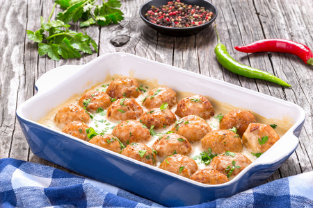 smothered: meatballs smothered in a creamy gravy sauce, close-up Stock Photo