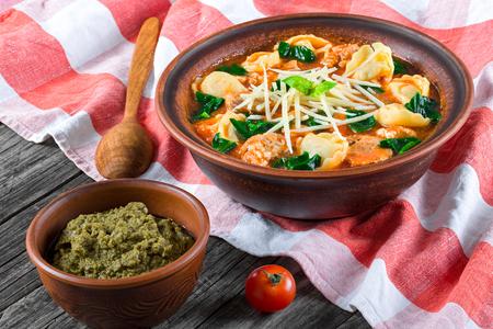 Tortellinisuppe mit italienischen Würstchen, Spinat, Tomate, Parmesankäse Standard-Bild - 56361777