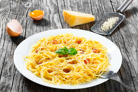 grated parmesan cheese: Spaghetti carbonara, basil, eggs yolk, grated parmesan cheese, bacon, close-up