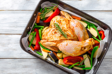 whole chicken: raw whole chicken with colorful pieces of peppers, potatoes.  close-up Stock Photo