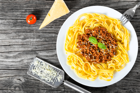 recipe decorated: Bolognese ragout with italian pasta on a white plate, decorated with basil leaves, authentic recipe, wooden background with celery, garlic, cherry tomatoes and parmesan cheese, full focus, close-up