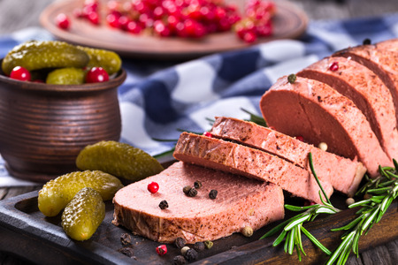 liver pate with red currants, pickles and spices on a black board, close-up