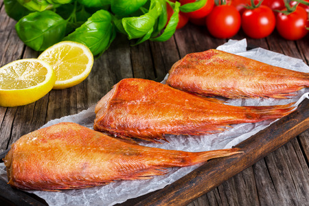 Red Sea Bass on a parchment paper on an old wooden table with basil leaves, lemon slices and cherry tomatoes on the background, horizontal close-up, top view Standard-Bild