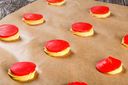 shu: dough with red strawberry crumble for baking cakes shu eclairs on a parchment paper, classic french recipe, close-up
