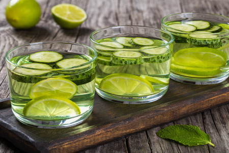 fat burning: Very Fat Burning Detox Drink - Sassy Water: sliced cucumber, lime, ginger and mint in the three glasses on a wooden tray on an old wooden table, close-up Stock Photo