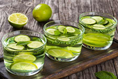 sassy: The Most Efficient Drink For Losing Belly Fat - Sassy Water: sliced cucumber, lime and mint in the three glasses on a wooden tray on an old wooden table, close-up