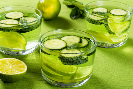 fat burning: Very Fat Burning Detox Drink - Sassy Water: sliced cucumber, lime and mint in the three glasses on a green  table rib mat, close-up