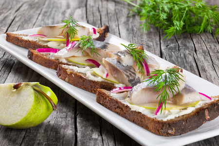 sandwich with herring fillets, onion, pickled cucumber and dill on parchment paper on an oval dish on an old rustic table, traditional street food in Norway, close-up Archivio Fotografico