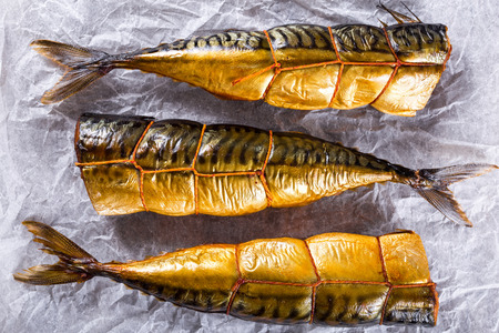Smoked fish Mackerel or Scomber on a white parchment paper, studio lights, close-up, top view Archivio Fotografico