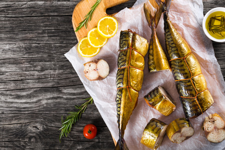 smoked: Slices of Smoked fish Mackerel or Scomber on a white parchment paper with cherry tomato, sliced lemon and rosemary on an old wooden table with small bowl with olive oil, studio ligths, top view