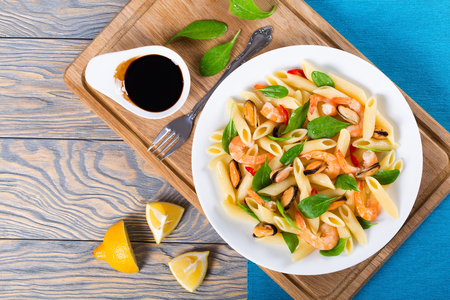 penne pasta salad with shrimps, mussels and baby spinach Archivio Fotografico