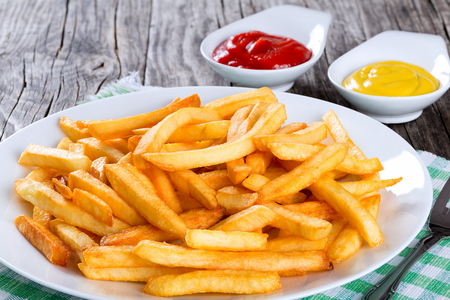 Tasty french fries on a white plate with mustard and tomato sauce in a gravy boat on wooden table background,  close-up