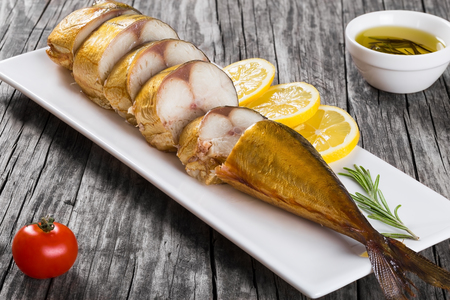 Slices of Smoked fish Mackerel or Scomber on a white rectangular dish with cherry tomato, sliced lemon and rosemary on an old wooden table, small bowl with olive oil, studio lights, top view
