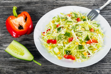 fat food: Healthy low calories spring cabbage salad with bell pepper, corn, cucumber and dill, on a white dish, studio lights, close-up, top view Stock Photo