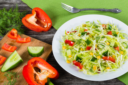 Healthy low calories spring cabbage salad with bell pepper, corn, cucumber and dill, seasoned with olive oil on a white dish. cutting board with chopped veggies on the background,  top view
