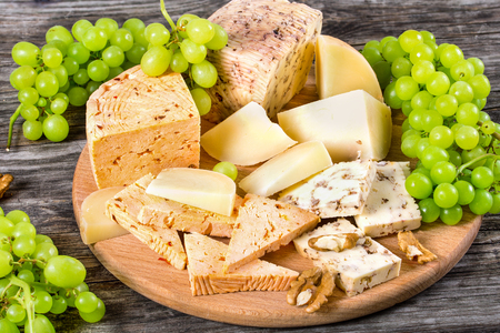 cheese plate: Cheese plate: organic  homemade goat cheese with walnuts and spices. Green Grapes and walnuts on an old rustic background, studio lights, close-up