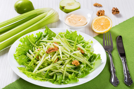 american cuisine: Studio macro of Salad with Green apples, Celery and walnut  on a bed of lettuce on a white dish, on white wooden background, american cuisine, view from above