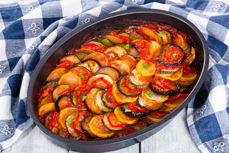 Layered ratatouille in a baking dish, slices of zucchini, red bell pepper, chili, yellow squash, eggplant, olive oil, parsley and garlic on a white background, close-up Archivio Fotografico