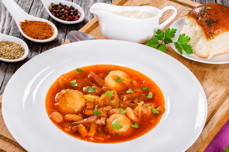 european cuisine: East European cuisine. Ukrainian vegetable and meat soup borscht in a white wide rim dish, view from above, close-up