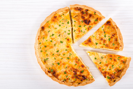 custard slices: onion cheese quiche or pie sprinkled with parsley and spring onion, cut into portion, on white table, top view, blank space left Stock Photo