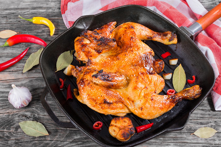 Grilled whole chicken marinated in honey and soy sauce in grill pan with garlic, bay leaves and pieces of chili on rustic table and kitchen towel, view from above Archivio Fotografico