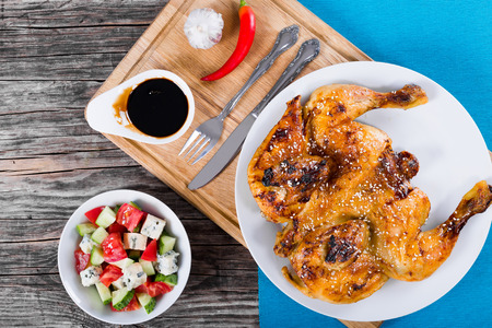 Grilled chicken on white dish on cutting board with fork and knife. Tomato, cucumber, blue cheese gorgonzola salad in white bowl, balsamic vinegar in gravy boat, view from above
