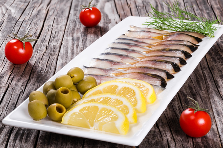 morsel: fish appetizer - slices of smoked and marinated mackerel or scomber on rectangular dish with sliced lemon, green olives and dill on old wooden table, close-up