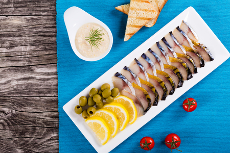 slices of smoked and marinated mackerel or scomber on dish with sliced lemon, green olives, toasts and horseradish, top view