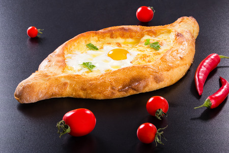 Ajarian khachapuri with egg on black background with cherry tomatoes and red chili pepper, authentic recipe, view from above, close-up