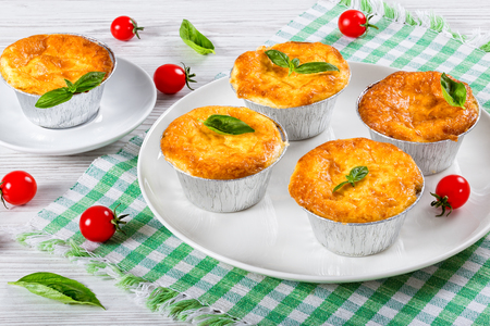 recipe decorated: French  dish julienne. Mushroom, chicken and cheese gratin in Aluminum Foil Mini Baking molds decorated with basil leaves and cherry tomatoes, on white plate,  authentic recipe,close-up Stock Photo